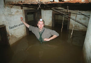 Berlin city planner Dietmar Arnold, 31, stands hip-deep in the water-filled concrete bunker under Alexanderplatz in former East Berlin in summer, 1995.
