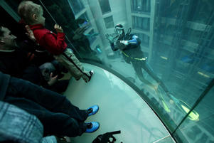 A diver cleaning the glass of a giant, cylindrical aquarium waves to visitors at the AquaDom in Berlin, Germany.
