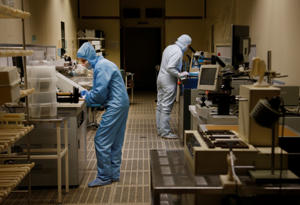 Workers at the Semiconductor Devices Factory control manufacturing operations for the production of electronic components in Minsk, Belarus, March 31, 2015.