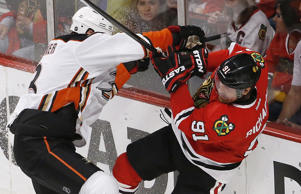 Anaheim Ducks defenseman Clayton Stoner, left, checks Chicago Blackhawks center Brad Richards during the second period in game four of the Western Conference finals May 23 in Chicago.