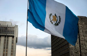 The Guatemalan flag flies between the Bank of Guatemala building and the Justice Tower in Guatemala City, Guatemala,