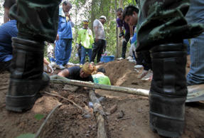 Rescue workers inspect a mass grave at a rubber plantation near a mountain in Thailand's southern Songkhla province May 6, 2015.
