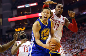 Golden State Warriors guard Stephen Curry drives to the basket before being fouled by Houston Rockets center Dwight Howard (right) during game three of their Western Conference finals matchup in the NBA playoffs on May 23, 2015, in Houston.