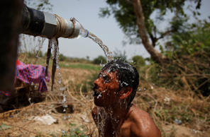 An Indian man takes bath under the tap of a water tanker on a hot day in Ahmadabad, India, Thursday, May 21, 2015. Heat wave conditions prevailed as temperature rises in many parts of India.
