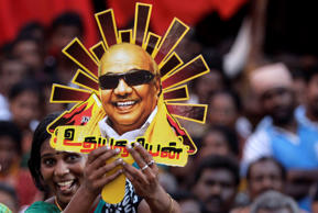 File: A supporter holds up a cutout with a portrait of Dravida Munnetra Kazhagam (DMK) party chief M. Karunanidhi during an election rally in Chennai, India, Tuesday, April 22, 2014. The multiphase voting across the country runs until May 12, with results for the 543-seat lower house of Parliament announced May 16.
