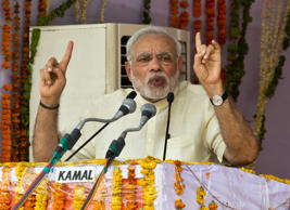 Indian Prime Minister Narendra Modi addresses people at the birth place of Denndayal Upadhyay, one of the main ideologists of Rashtriya Swayamsevak Sangh (RSS), a militant Hindu group, on the eve of the ruling BJP government's first anniversary at Nagla Chandrabhan, India, Monday, May 25, 2015