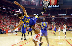 Golden State Warriors guard Stephen Curry topples over Houston Rockets forward Trevor Ariza during the first half in Game 4 of the Western Conference finals of the NBA basketball playoffs, Monday, May 25, 2015, in Houston.