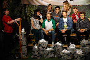 A Madame Tussauds tissue attendant hands One Direction fans Tansy Ratcliffe-James, Laura Tokely and Lindsay Ringette tissues in London, England.