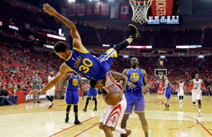 Golden State Warriors guard Stephen Curry topples over Houston Rockets forward Trevor Ariza during the first half in Game 4 of the Western Conference finals of the NBA basketball playoffs, Monday, May 25,  in Houston.