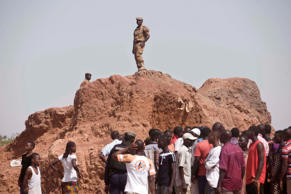 Security forces, top, keep watch near the Dagnoen Cemetery, as the graves of thirteen people including Burkina Faso revolutionary leader Thomas Sankara, are exhumed on the outskirts of Ouagadougou, Burkina Faso, Monday, May 25, 2015.