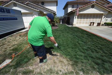 Cy Bodden from LawnLift sprays their Grass Paint product to enhance the green color as water restrictions take their toll during a severe drought in San Diego and California on May 12, 2015.