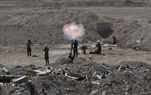 Members of the Iraqi army and Shi'ite fighters launch a mortar toward Islamic State militants outskirt the city of Falluja, Iraq May 19, 2015. Iraqi security forces on Tuesday deployed tanks and artillery around Ramadi to confront Islamic State fighters who have captured the city in a major defeat for the Baghdad government and its Western backers.