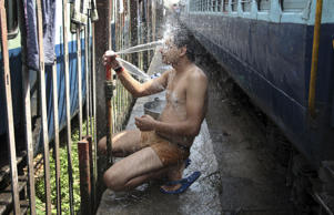 An Indian passenger takes a bath beside rail tracks on a hot summer day at a railway station in Jammu, India.