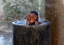 A girl bathes to cool off herself with water that is leaking from a broken pipe valve on a hot summer day on the outskirts of Ahmedabad, India, May 18, 2015.