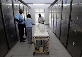 File: Relatives of a HIV-AIDS victim stand next to a body for inspection in Port Moresby General Hospital's morgue.