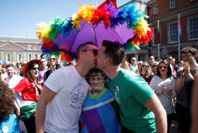Europe And Africa Week In Pictures - FILE - In this file photo dated Saturday, May 23, 2015, two men kiss as first results start to filter through in the country's referendum over the legalization of gay marriage, as the crowds wait for declared results in Dublin, Ireland. The kissing couple hold a card figure of female comedy character Agnes Brown, played by male actor Brendan O'Carroll in Irish TV show Mrs. Brown's Boys.  Ireland has voted resoundingly to legalize gay marriage in the world's first national vote on the issue.   (AP Photo/Peter Morrison, FILE)