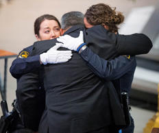 Two Omaha police officers embrace Hector Orozco, the husband of Kerrie Orozco, near the end of her funeral service Tuesday, May 26, 2015 at St. John's Catholic Church at Creighton University in Omaha, Neb. Orozco, 29, was shot and killed May 20, 2015 in Omaha. (Matt Miller/The World-Herald via AP, Pool)