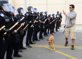 A protester walks his dog in front of Albuquerque Police officers in full riot gear blocking 5th Street in Downtown Albuquerque to prevent protesters from continuing the march, March 30, 2014.