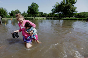 Nayeli Cervantes carries her friend's daughter Sophia Aviles through the floodwaters outside their apartment in Houston, Tuesday, May 26, 2015. Heavy rain overnight cause some major highways to be closed in the Houston area.