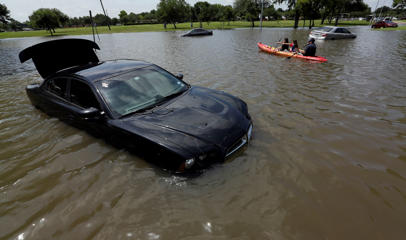 Domingo Molina, right, paddles with his granddaughters Crystal, left, and Alicia, center, down a flooded street in Houston, Tuesday, May 26, 2015.