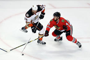 Ryan Getzlaf #15 of the Anaheim Ducks skates with the puck as Niklas Hjalmarsson #4 of the Chicago Blackhawks defends in Game Six of the Western Conference Finals during the 2015 NHL Stanley Cup Playoffs at the United Center.