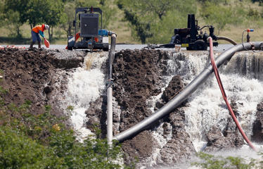 Workers tend to equipment used to pump water from Padera Lake as water pours over a temporary dam on May 27, 2015 in Midlothian, Texas. Officials feared that the temporary dam on Padera Lake would fail due to recent heavy rains in the area.