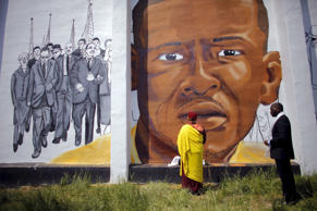 Gyalwang Drukpa (C), a Buddhist leader from South Asia, prays in front of a mural of Freddie Gray in Baltimore, Maryland,