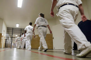In this, Monday, Sept. 23, 2013, file photo, inmates walk the halls in formation at Tutwiler Prison for Women in Wetumpka, Ala.  On Thursday, May 28, 2015, the Justice Department filed both a civil lawsuit against the state and a settlement agreement to address the alleged abuses at the Julia Tutwiler Prison for Women. State officials have agreed to install monitoring cameras, increase privacy in bathrooms, hire more staff and implement new procedures to ensure inmate complaints are taken seriously.
