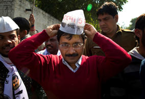 File: Aam Aadmi Party, or Common Man Party, leader Arvind Kejriwal, adjusts his cap while campaigning ahead of Delhi state elections in New Delhi, India, Thursday, Feb. 5, 2015.