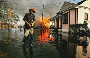 Robert Fontaine walks past a burning house fire in the 7th ward September 6, 200...