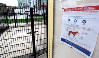 In this April 16, 2015, file photo, a sign warning of canine respiratory illness is posted at a dog park in Chicago.