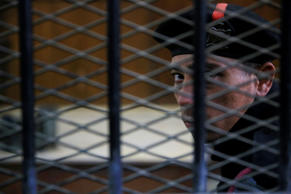 An Egyptian policeman guards the courtroom defendant's cage during the verdict hearing in a case rooted in violence that swept the country after the military-led ouster of Islamist President Mohammed Morsi in 2013, in Cairo, Egypt, Saturday, April 11, 2015.