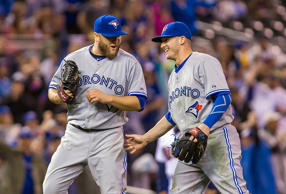 Blue Jays third baseman Josh Donaldson (20) congratulates starting pitcher Mark Buehrle (56) on a complete game win against the Twins. The Jays beat the Twins 6-4.