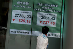 A passerby looks at a panel displaying the blue-chip Hang Seng Index outside a bank during afternoon trading in Hong Kong, China May 28, 2015.