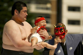 A ring assistant wears a mask to scare a baby held by an amateur sumo wrestler during a baby crying contest at Sensoji temple in Tokyo on May 30, 2015. In the contest, two wrestlers each hold a baby while a referee makes faces and loud noises to make them cry. The baby who cries the loudest wins. The ritual is believed to aid the healthy growth of the children and ward off evil spirits. One hundred and twenty children took part in the event, the organizer said.