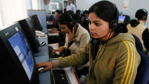 Employees at a call centre provide service support to customers in the northeastern Indian city of Siliguri.