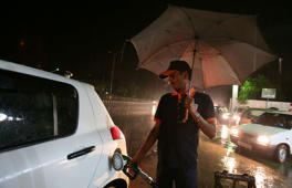 A worker fills a car with petrol at a fuel station as it rains.