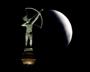 A partially-eclipsed full moon sets behind a statue of a Kansa Indian at the Kansas Statehouse, Saturday, April 4, 2015 in Topeka, Kan.