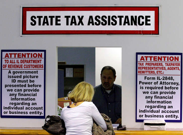 In this April 16, 2012 file photo, an Illinois Department of Revenue employee offers assistance to income tax payers at the Illinois Department of Revenue in Springfield, Ill. The widening gap between the wealthiest Americans and everyone else has been matched by a slowdown in state tax revenue, according to a report being released Monday, Sept. 15, 2014 by Standard & Poor's. Seth Perlman/AP Photo