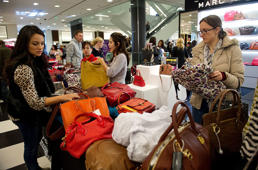 Shoppers browse handbags on sale at a Bloomingdale's store in the Westfield San Francisco Centre in San Francisco, California, U.S., on Friday, Nov. 23, 2012. To get shoppers to spend more than last year, retailers have continued to turn Black Friday, originally a one-day event after Thanksgiving, into a week's worth of deals and discounts.
