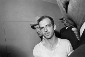 FILE - In this Nov. 23, 1963 file photo, Lee Harvey Oswald is led down a corridor of the Dallas police station for another round of questioning in connection with the assassination of U.S, President John F. Kennedy. Oswald, who denied any involvement in the shooting, was formally charged with murder. (AP Photo)