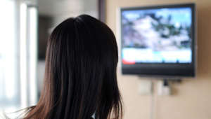 A woman watching television.