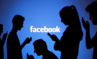 People are silhouetted as they pose with mobile devices in front of a screen projected with a Facebook logo.