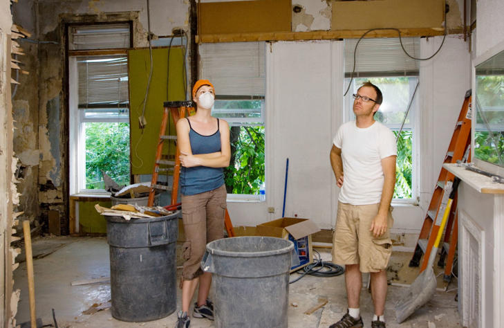 Couple standing in room under renovation.