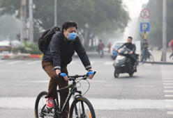 A cyclist wearing a mask on a heavily polluted day in Beijing. The soaring, grimy chimneys of the coal-fired power station have belched the last of their choking fumes into Beijing's air, authorities say -- but experts doubt the plan will ease the capital's smog.