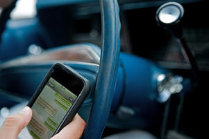 Person driving and using cellphone. Image Source/Getty Images
