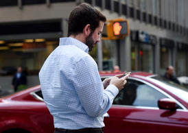A man uses his smartphone while waiting at a street corner on November 13, 2014 in New York.