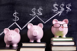 Three pink piggy banks standing on books next to a blackboard with simple savings progress chart.  Sharp focus on the piggy banks.  Alternative version shown below: