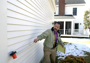 Appraiser Cristophe Karageorge measures the side of a home in Cape Elizabeth today to aid his information for appraising this home for the owner.