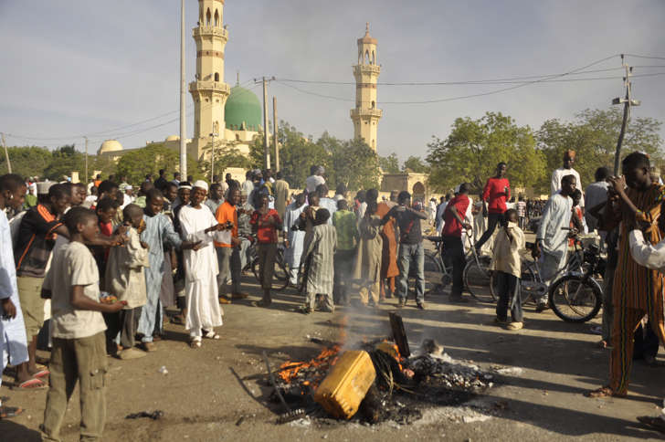 People gather at the site of a bomb explosion in Kano, Nigeria on Friday.